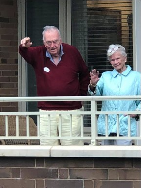 The Cardinal residents standing and waving on balconies to celebrate while socially distancing.